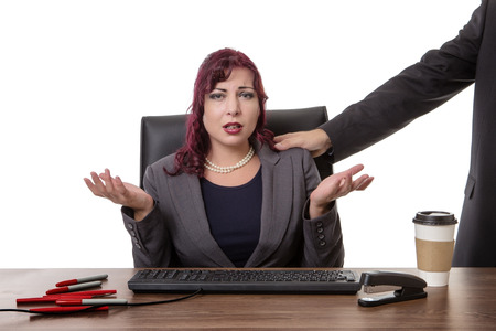secretary sitting at desk with a mans hand on her shoulder  feeling uncomfortable