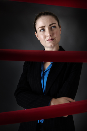 low key lighting: business woman caught behind red tape shot in the studio with low key lighting Stock Photo