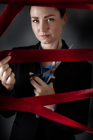 low key lighting: business woman caught behind red tape cutting her way free,  shot in the studio with low key lighting