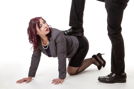 business woman crawling along the floor with a mans foot resting on her bottom