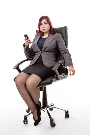 handcuffing: Studio shot with a business woman handcuffed to an office chair Stock Photo