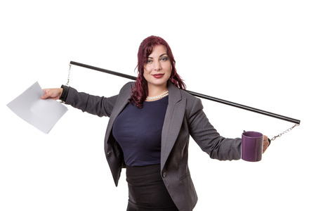 handcuffed: Business Woman with hands out to the side handcuffed to a pole, also holding a blank sheet of paper and a coffee cup.