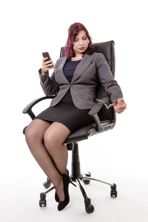 handcuffed: Business woman sitting down having been handcuffed to an office chair