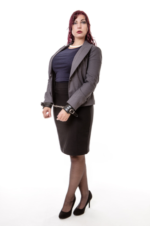 forlorn: woman in a suit with her hands handcuffed at the front.