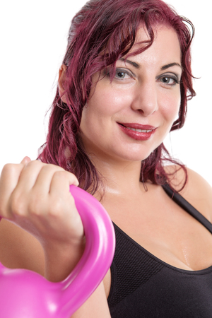 kettle bell: Portrait close up of young attractive female doing kettle bell exercise on grey background. Fitness woman working out. Crossfit exercise. Stock Photo