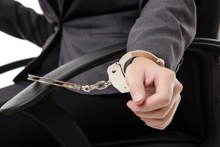 Photograph of womans hand in handcuffs (close-up) cuffed to an office chair.