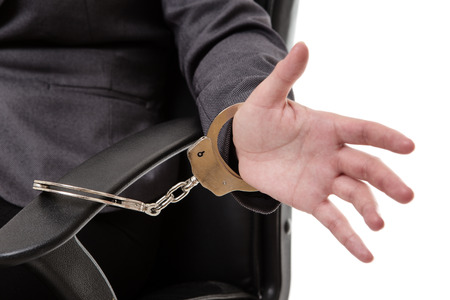 handcuffing: Woman in a business suit handcuffed to an office chair with an open hand.