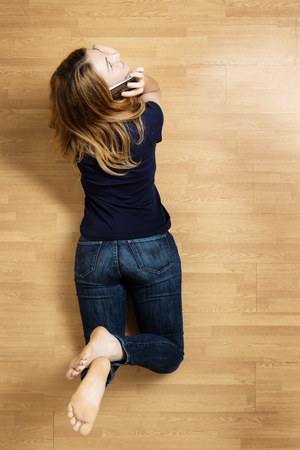 Woman lying on the floor on her stomach using her mobile phone