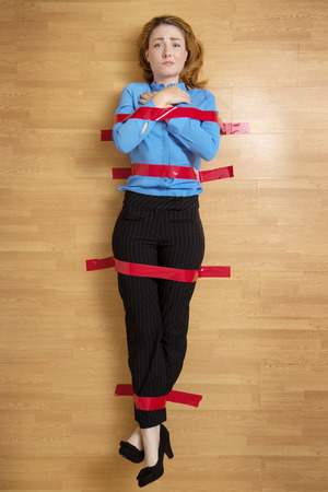 restrained: Business woman stuck to the floor with red tape, hands clasped to her chest Stock Photo