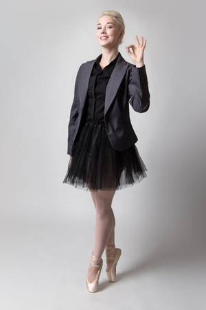en pointe: Model in suit jacket and a ballerina tutu, making the ok hand gesture