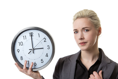 timezone: Woman in a suit holding a large clock looking worried