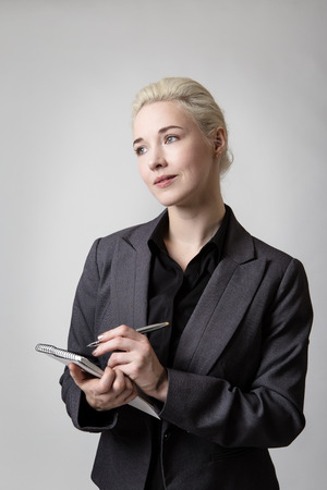 woman only: Model holding a spiral notepad and pen, poised to write