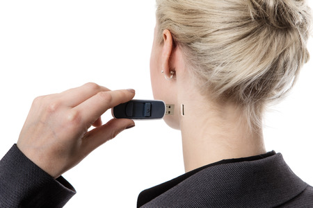 memory stick: shot from behind of a woman holding a memory stick putting it in the side of her neck