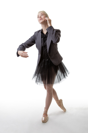 poised: Studio shot of a ballerina model holding a phone to her left ear, with her right arm poised infront of her Stock Photo