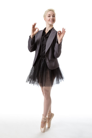 en pointe: Model in a ballerina tutu, making the ok hand gesture with both hands