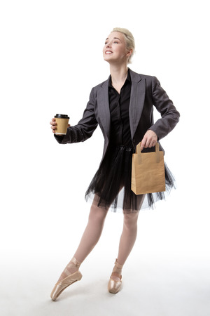 paperbag: Studio shot of a ballerina model holding a takeaway cup in her right hand and a paperbag in her left hand.