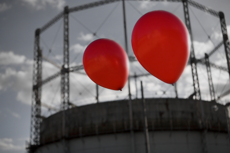 uplifting: Two ballons flying over a gas storage tank