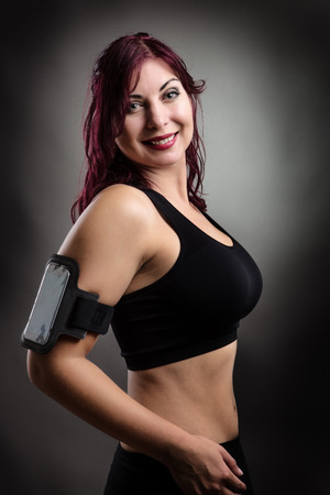 low key lighting: happy fitness woman with a phone holder around her arm ready to go for a run shot in the studio low key lighting