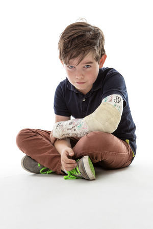 broken arm: Young boy is sitting down and unable to join in because he has broken his arm Stock Photo