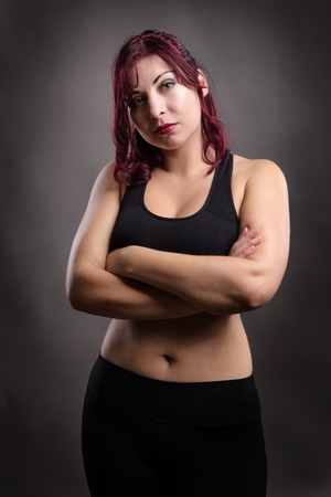 low key lighting: low key lighting set up of plus size fitness model standing in studio not looking very happy with her arms crossed Stock Photo