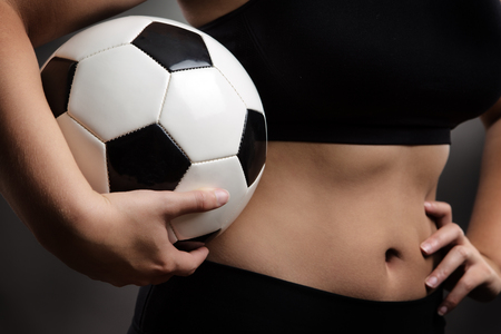 midriff: close up shot of womans midriff holding a football in her hand