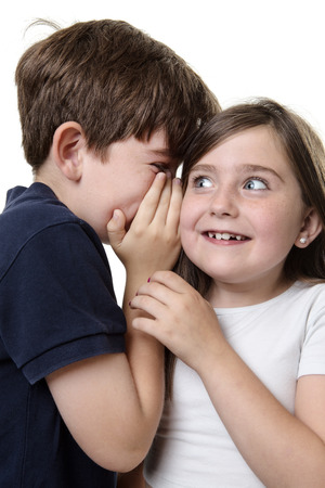 two children whispering into each others ear sharing a secret! Stock Photo