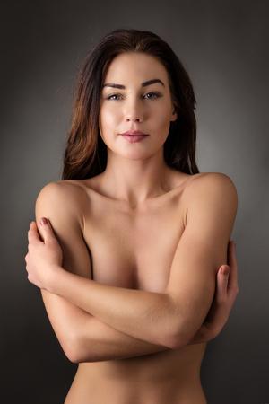 nudo integrale: attraente donna nuda che copre il suo colpo seno in studio