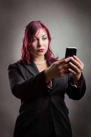 judging: Business woman holding her mobile phone out in her hands and checking out her reflection