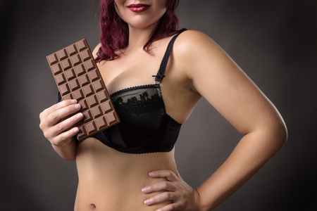 voluptuous woman holding a bar of chocolate in her underwear Stock Photo