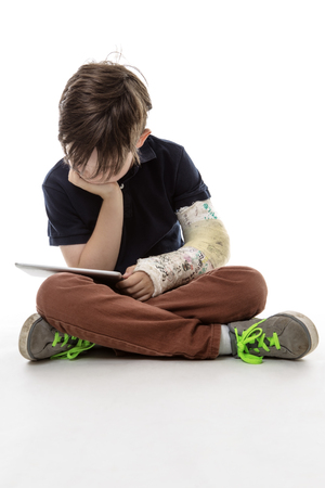 legs folded: Young boy is sitting on the floor reading his tablet computer witha broken arm