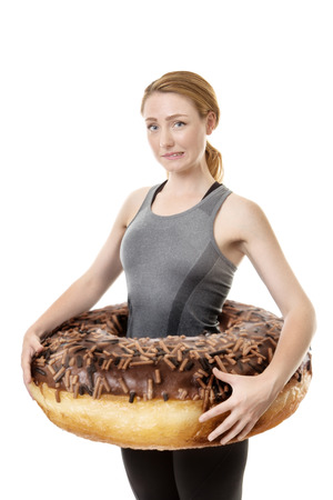 fitness woman with a large donut around her waist symbolize putting on weight