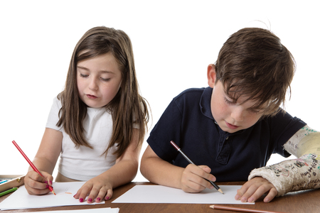 next to each other: Two children sitting next to each other drawing Stock Photo