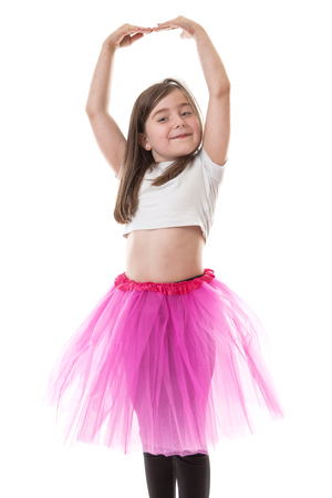 arms above head: Pretty young girl in a bright pink tutu with her arms raised above her head.