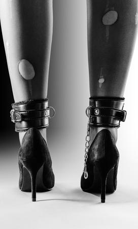 Fußketten um eine Frau, die Beine tragen High Heels