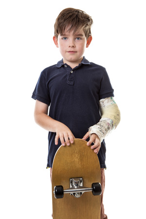 cast: Young lad cant use his skateboard as he has broken his left arm. Stock Photo