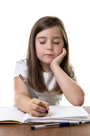 studious: Studious young girl is trying hard with her homework Stock Photo