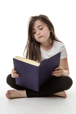 kid reading: pretty young girl is sitting cross legged whilst reading her book isolated on white Stock Photo