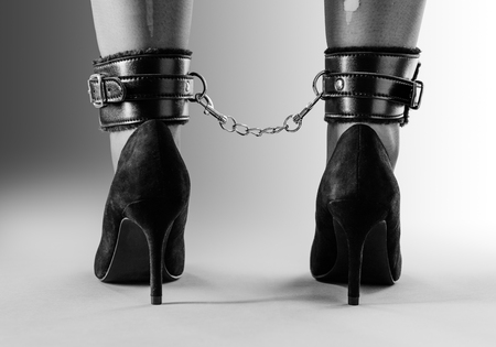 ankle chains around a woman legs wearing high heels