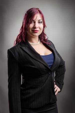 Retrato de estudio de una mujer de negocios confía y sonriente feliz de pie con la mano izquierda a su vestimenta corporativa de cadera