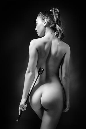 femme noire nue: �clairage faible cl� de l'arri�re d'une femme sexy tenant un fouet Banque d'images
