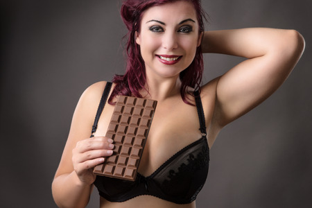 voluptuous: voluptuous woman holding a bar of chocolate in her underwear Stock Photo