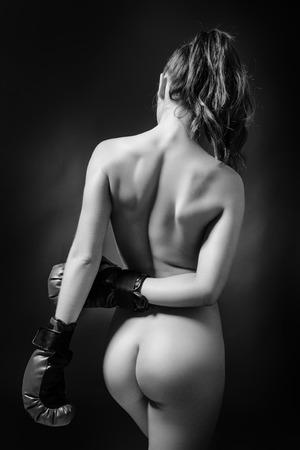 mujer desnuda de espalda: iluminación de bajo perfil de la parte posterior de una mujer atractiva con guantes de boxeo Foto de archivo