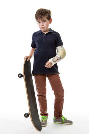broken arm: Full length portrait of a cute young boy holding a skateboard with a broken arm  isolated on white background