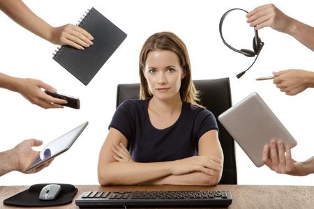 femme d'affaires accablé assis à son bureau entouré par de nombreuses mains tenant des objets différents Banque d'images