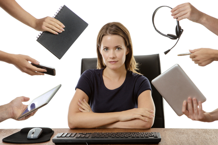 overwhelmed business woman sitting at her desk surrounded by many hands holding different objects Imagens