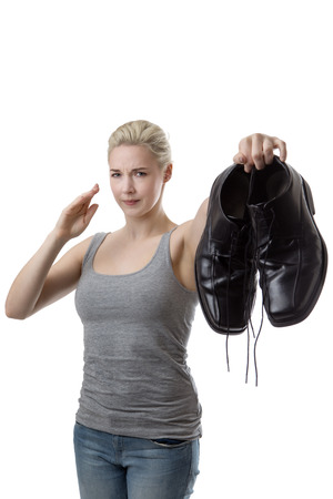smelly: woman holding up a pair of mens smelly shoes not looking very happy