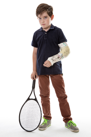male arm: Shot of a cute young boy who has broken his left arm and is unhappy because he cant play tennis