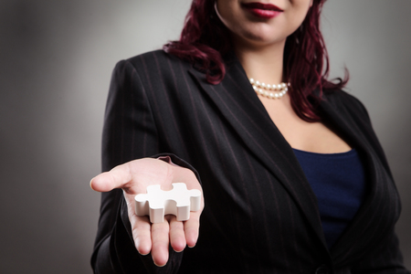 stretched out: Close up studio shot of a woman holding a 3d puzzle piece in the open palm of her right hand, arm out stretched