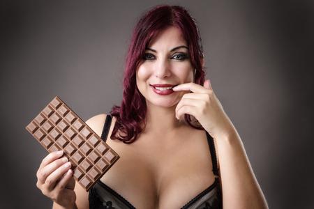 voluptuous: voluptuosa mujer que sostiene una barra de chocolate en su ropa interior Foto de archivo