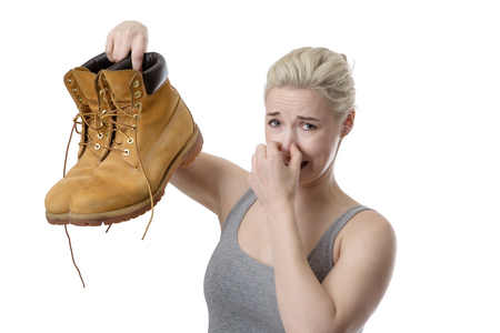 woman holding up a pair of mens smelly shoes not looking very happy